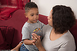 5 year old boy at home with mother, sitting with her and talking, fingers interlaced