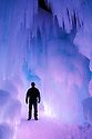 Towering pillars of ice form passages and corridors bathed in colored lights inside the Ice Castle at Loon Mountain.