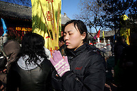 CHINA. A woman praying during Chinese New Year in Baiyun Temple in Beijing.  Chinese New Year, or Spring Festival, is the most important festival and holiday in the Chinese calendar In mainland China, many people use this holiday to visit family and friends and also visit local temples to offer prayers to their ancestors. The roots of Chinese New Year lie in combined influences from Buddhism, Taoism, Confucianism, and folk religions.  2008..