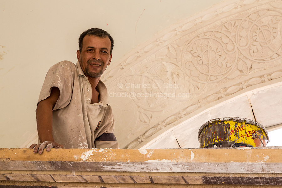 Senegal, Touba.  Moroccan Craftsman Taking a Break from Carving a Design into an Arch inside the Grand Mosque.