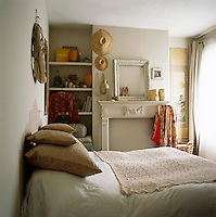 A white bedroom with a double bed covered in a crocheted blanket. An empty picture frame is placed upon the mantelpiece echoing the empty fireplace below