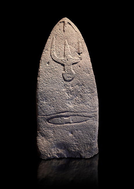 Late European Neolithic prehistoric Menhir standing stone with carvings on its face side. The representation of a stylalised male figure starts at the top with a long nose from which 2 eyebrows arch around the top of the stone. below this is a carving of a falling figure with head at the bottom and 2 curved arms encircling a body above. at the bottom is a carving of a dagger running horizontally across the menhir. Excavated from Genna Arrele II. Menhir Museum, Museo della Statuaria Prehistorica in Sardegna, Museum of Prehoistoric Sardinian Statues, Palazzo Aymerich, Laconi, Sardinia, Italy. Black background.