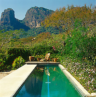 A view of the mountains beyond the swimming pool which is surrounded by orange trees and jasmine