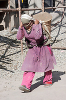 Kathmandu, Nepal.  Nepali Woman Carrying Basket of Sand for Mixing with Cement.