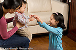 16 month old toddler boy held by mother anticipating tickle from 8 year old sister laughing horizontal.EVOstock
