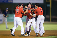 Brett Austin (middle) is mobbed by teammates Ethan Gross (18), Eddy Alvarez (1) and others after hitting a walk-off 2-run double in the bottom of the ninth inning against the Asheville Tourists at Intimidators Stadium on June 25, 2015 in Kannapolis, North Carolina.  The Intimidators defeated the Tourists 9-8.  (Brian Westerholt/Four Seam Images via AP Images)
