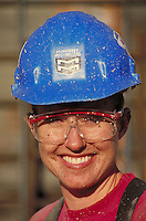 Portrait of smiling, debris-splattered female construction worker wearing protective hardhat and goggles. California.