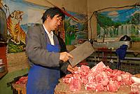 Butcher chops yak meat in the Tibetan quarter, Lhasa, Tibet.