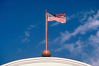 United States Flag flying on top of building.