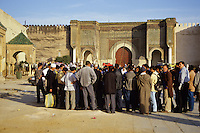 Meknes, Morocco.  Place Hedime.  An Audience Surrounds a Storyteller.  Bab Mansour in Background, built 1672-1732, entrance to the imperial quarter.