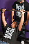 Education High School physical education elective weight lifting teenager lifting bar, spotter behind him
