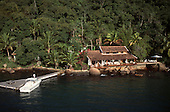 Ilha Grande, Brazil. Luxury modern holiday house built close to the sea with veranda and hammocks, motor boat.