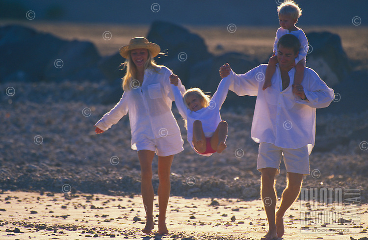 Happy family on vacation walking on the beach