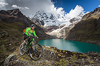 Downhill mountain biker with Cordillera Huayhuash in the background.
