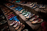 Slippers belonging to monks from the Myazeda Man Oo Monastery, where they produce promotional material and literature for the Buddhist nationalist 969 movement, are lined up outside the prayer hall while the monks pray in Mawlamyine, Mon State. /Felix Features