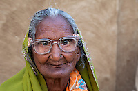 Bharatpur, Rajasthan, India.  Old Woman Sitting in Front of her House.  She wears a dupatta (scarf) over her head and shoulders.