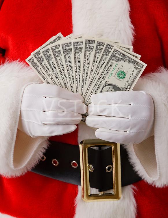 USA, Illinois, Metamora, Studio shot of Santa holding fan of one dollar banknotes, mid section