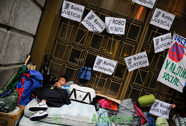 Joseph lies on a mattress outside a branch of Caja Madrid, part of the Bankia group bailed out by the Spanish state, during a protest against evictions on the Plaza Celenque in Madrid on October 25, 2012. A man in Spain hanged himself shortly before bailiffs came to evict him, police said today, prompting angry protestors to call him a victim of predatory mortgage lenders. Protestors demonstrating in the capital against evictions outside the office of Caja Madrid -- a major mortgage lender now part of the Bankia group -- held a minute's silence for the man, whom they named as Jose Luis Domingo.  (c) Pedro ARMESTRE