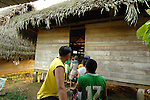 On a Sunday afternoon,  locals in Midway village, southern Belize, line up outside a thatched home where the owner is playing a Kung Fu video on his new VCR.  The floor inside the hut is also packed with children and adults watching the action movie.