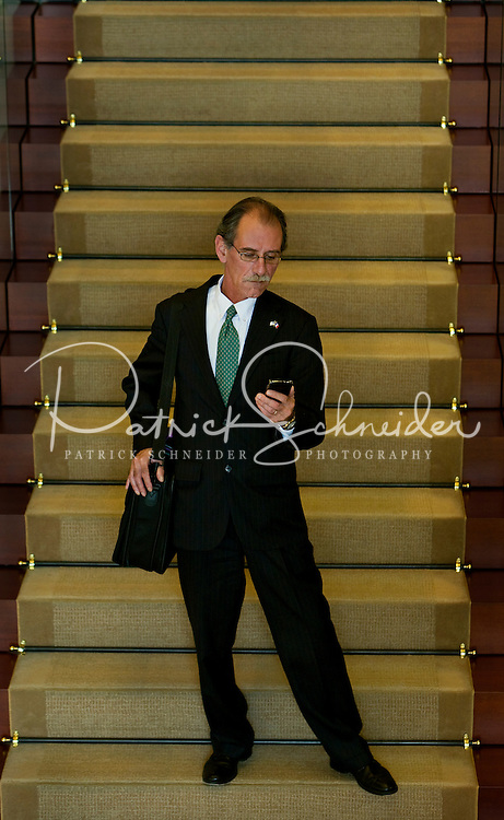 A man pauses on a staircase while checking his email on a mobile PDA. Model is model released.