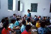 A woman schoolteacher teaches eight - and nine-year-old boys in a religious school in Bangladesh. Students recite the day's lesson as classmates listen. Dhaka, Bangladesh Asia.
