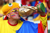 A Colombia fan kisses a replica World Cup trophy