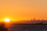 The sun sets in the west, behind a backdrop of the San Francisco skyline and bay, at the same moment the Full Buck Moon rises in the east.