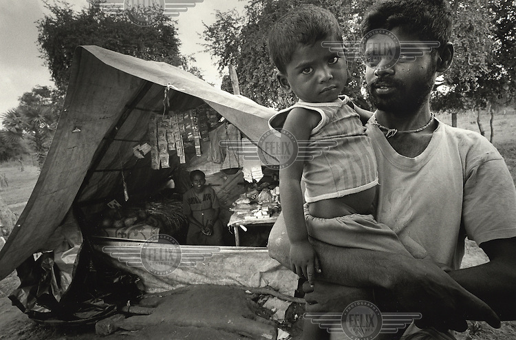 """Mukuuthan Sutharshini waits in her shop for customers with her husband and son. """"We came back two months ago. Business is not so good even though this is the only shop in the village because there are not many people. Too many were killed in the war. There are not many left."""""""
