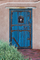 Rustic blue door in wall to New Mexico courtyard