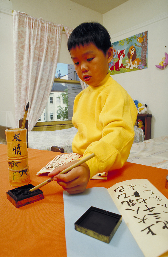 CHINESE-AMERICAN BOY PRACTICING HIS CALLIGRAPHY. CHINESE-AMERICAN CALLIGRAPHY STUDENT. SAN FRANCISCO CALIFORNIA USA.