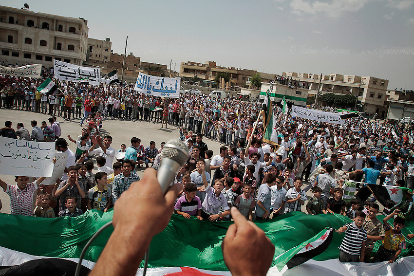 """Residents from the northern Syrian town of Al Bab organized a peaceful protest at a main square renamed after the revolution began as """"Freedom Square"""". Thousands of people gathered to sing and chant anti-Assad slogans - minutes later, the square emptied as the sound of a fighter jet from the Assad air force began to circle over the city. As the people scattered, a blast was heard followed by three other explosions. The fighter jet made at least 6 passes as it fired its 50 caliber  machine gun on the neighborhood below. Doctors at the local underground hospital did not allow this reporter access to the facility because of the load of patients coming in. Unconfirmed reports by the FSA spokesperson in Kilis say that 7 people died and 50 were injured. ..Photo: Javier Manzano / August 31, 2012"""