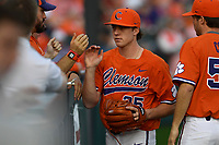 Relief pitcher Ryan Miller (35) of the Clemson Tigers is congratulated after a scoreless inning in a game against the William and Mary Tribe on February 16, 2018, at Doug Kingsmore Stadium in Clemson, South Carolina. Clemson won, 5-4 in 10 innings. (Tom Priddy/Four Seam Images)