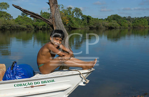 Xingu Indigenous Park, Mato Grosso State, Brazil. Aldeia Matipu; boy sitting on the 'Coracao do Brasil' boat at the port.