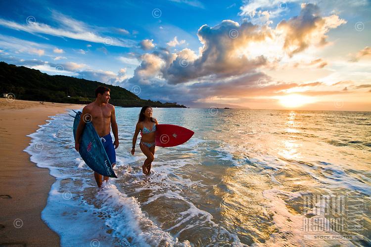 Silhouette of surfer couple at sunset at Waimea Bay Beach Park, Oahu