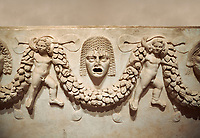 "Close up picture of Roman relief sculpted Sarcophagus of Garlands, 2nd century AD, Perge. This type of sarcophagus is described as a ""Pamphylia Type Sarcophagus"". It is known that these sarcophagi garlanded tombs originated in Perge and manufactured in the sculptural workshops of Perge. Antalya Archaeology Museum, Turkey.. Against a warm art background."