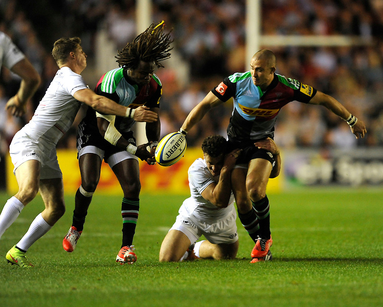 Marland Yarde of Harlequins fumbles the pass from Mike Brown of Harlequins as he is tackled during the Premiership Rugby Round 2 match between Harlequins and Saracens at The Twickenham Stoop on Friday 12th September 2014 (Photo by Rob Munro)