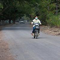 Myanmar, Burma, near Bagan.   Motorcycle Rider Wearing Breathing Mask.