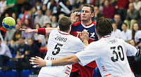 08 JAN 2012 - LONDON, GBR - Great Britain playmaker Chris Mohr (#7, in red) passes as he finds his path blocked by Austria's Vytautis Ziura (#5, in white) and Andreas Lassner (#30, in white) during the men's 2013 World Handball Championships qualification match at the National Sports Centre in Crystal Palace, Great Britain .(PHOTO (C) 2012 NIGEL FARROW)