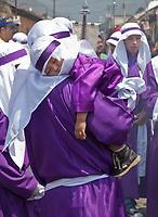 Antigua, Guatemala.  Cucurucho Carries his Sleeping Child during Holy Week, La Semana Santa.