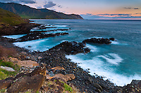 Sunset settles over the rocky shoreline of a beach in Makaha, O'ahu.