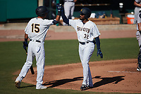 Johan Lopez (32) of the Charleston RiverDogs high fives teammate Michael Berglund (15) after hitting a home run against the Augusta GreenJackets at Joseph P. Riley, Jr. Park on June 27, 2021 in Charleston, South Carolina. (Brian Westerholt/Four Seam Images)