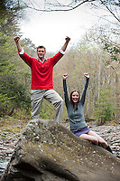 Young couple on large rock with arms in the air