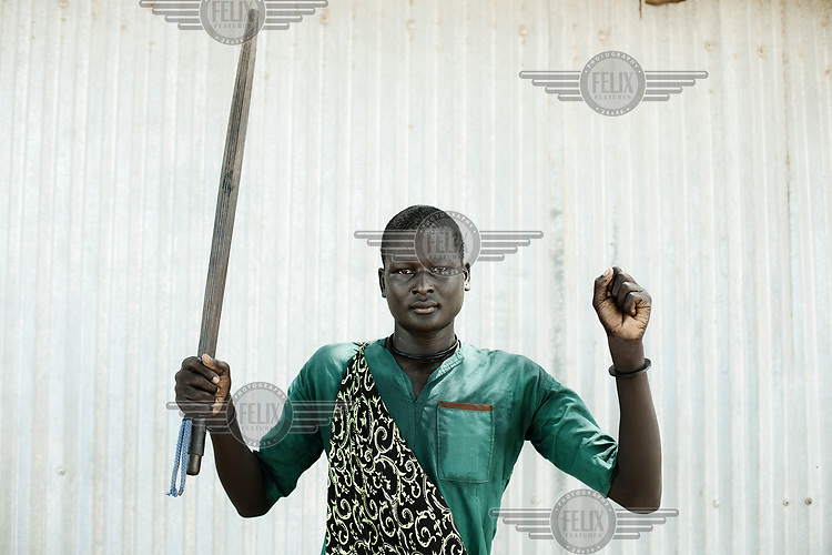 Choul Deng holds the weapon he uses to protect his cattle.