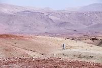 Morocco.  Man Riding Bicycle near Ait Benhaddou Ksar, a World Heritage Site.