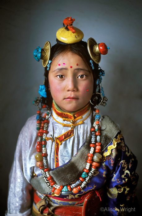 """Kham,Tibet<br /> This photo was featured in the magazine and made the cover the Taschen book celebrating 125 Years of National Geographic as well as my book, """"Face to Face: Portraits of the Human Spirit.""""<br /> I have been drawn to Tibet ever since I was child. When I moved to Nepal I discovered there were 120,000 refugees living throughout India and Nepal. I visited all 47 Tibetan refugee settlements and became consumed with documenting how the Tibetan people in exile have managed to maintain their culture despite not having a country.<br /> I have since made dozens of trips into Tibet, deep into the countryside as I follow the nomads. The photos and interviews became the basis of my Masters these in Visual Anthropology at U.C. Berkeley and two of my books, """"The Spirit of Tibet"""" and """"The Dalai Lama, A Simple Monk.""""<br /> On this particular trip I was driving in the remote eastern region of the Tibetan Plateau when I saw this young girl, part of a crowd returning from a horse festival. It was pouring rain, so I brought her to a nearby school to take her photograph She was so small that the light from the window barely reached her; I had to stand her on a desk. Even at the age of four, she had a face that seemed to express the underlying sadness of a culture that has been so challenged. Yet she had a look of resilience and tenacity well beyond her years."""
