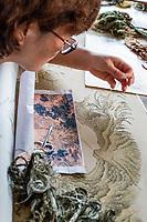 Suzhou, Jiangsu, China.  Young Woman Working on a Piece of Embroidery Art.