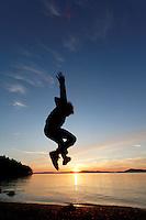 Girl leaping into the air above the setting sun, Sunset Beach, Washington Park, Anacortes, Skagit County, Washington