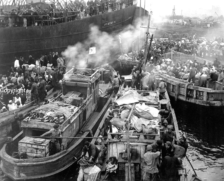 North Korean refugees use anything that will float to evacuate Hungnam.  Here they jam the decks of a South Korean LST and many fishing boats. December 19, 1950. (Navy)<br /> NARA FILE #:  080-G-424513<br /> WAR & CONFLICT BOOK #:  1480