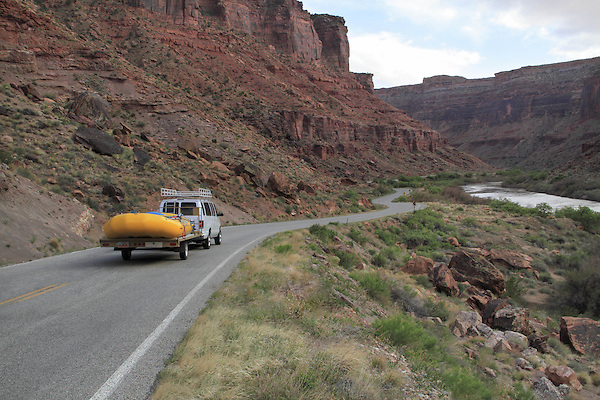 Van pulling whitewater raft on Highway 128 along the Colorado River near Moab, Utah, USA.