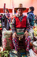 Chichicastenango, Guatemala.  Quiche (Kiche, K'iche') Man Wearing Embroidered Shirt and Pants, in Indoor Market, Sunday Morning.